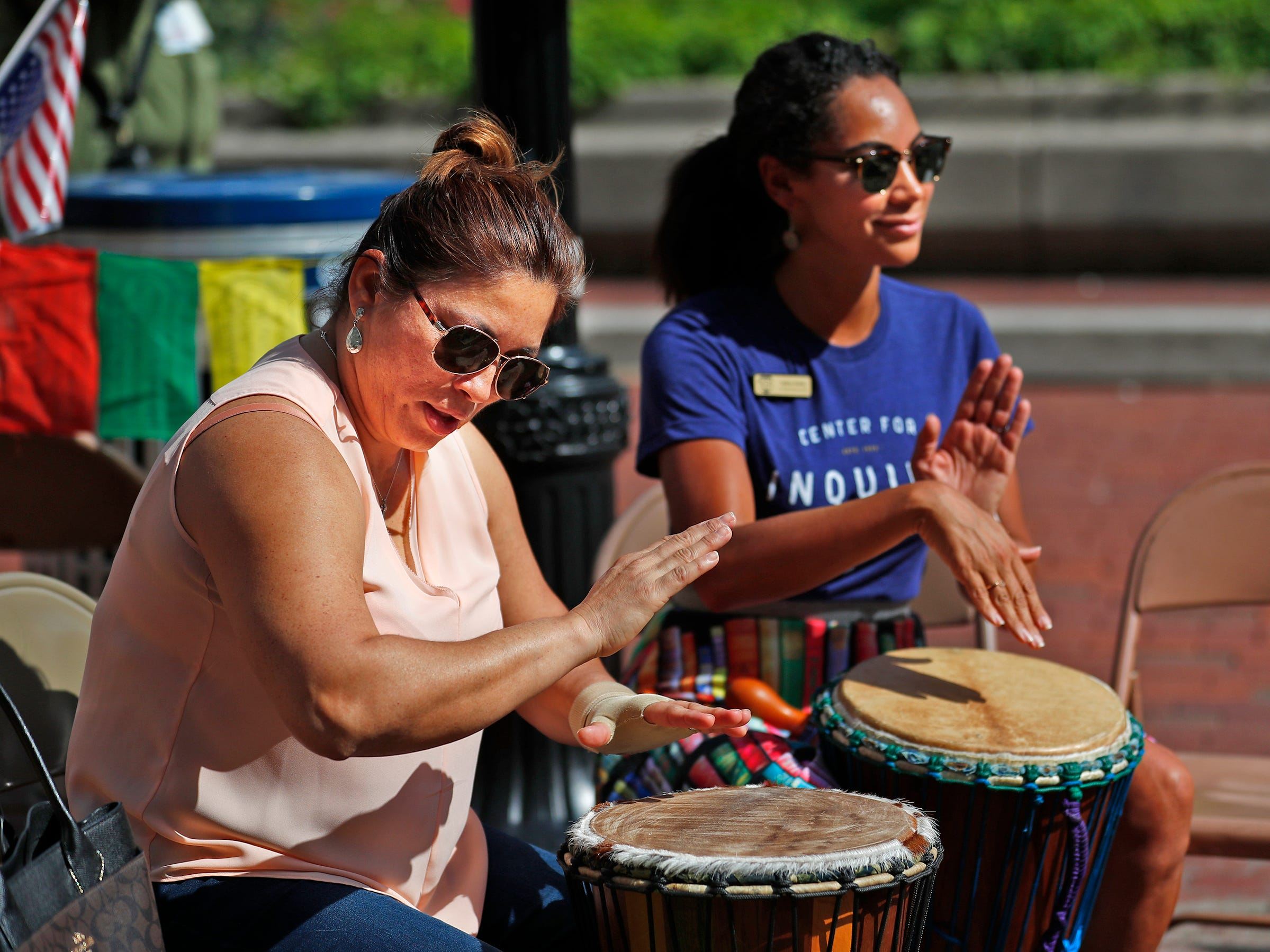 Selma Nieto, left, and Andrea Hunley play conga drums at the Center for Inquiry booth during the YMCA World Fest, on Monument Circle, Thursday, Sept. 13, 2018. YMCA of Greater Indianapolis hosts the free event that celebrates cultures including international food vendors, music, sports, and performers.