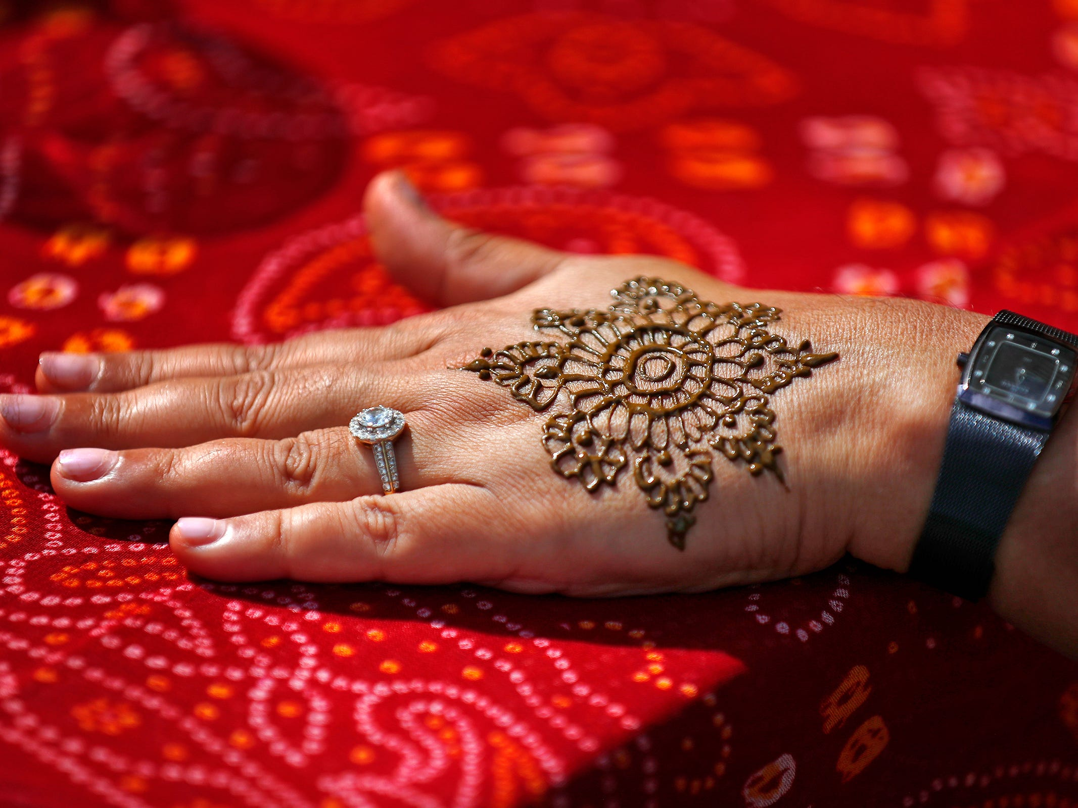 Rupal Thanawala shows her henna tattoo she got from Parul Shah, during the YMCA World Fest, on Monument Circle, Thursday, Sept. 13, 2018. They are both representing the Asian American Alliance at the event.  YMCA of Greater Indianapolis hosts the free event that celebrates cultures including international food vendors, music, sports, and performers.