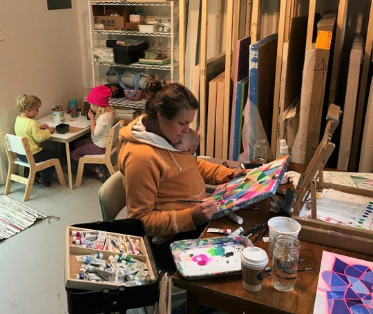 The professional artist home studios of mothers often look something like this one in Dallas, Texas.  Danielle Kimzey paints with her baby, Merritt, tucked inside her sweatshirt while her other children, June and Granville, create at their corner table. Her work is part of a new exhibit at Public Space One in Iowa City.