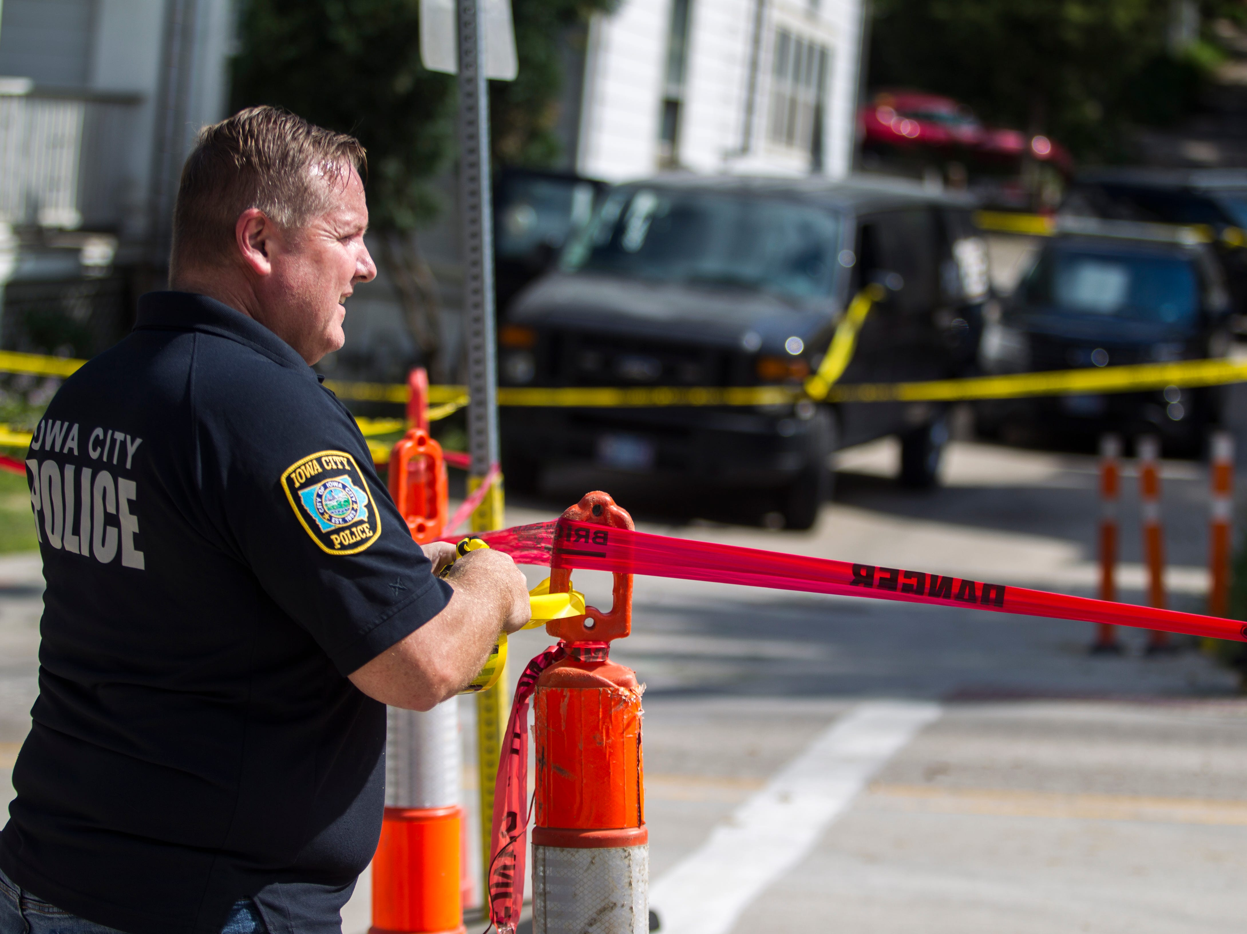 An Iowa City Police officer puts up yellow caution crime scene tape during an a motor vehicle collision investigation on Thursday, Sept. 13, 2018, along Dubuque Street between Brown and Church Streets.