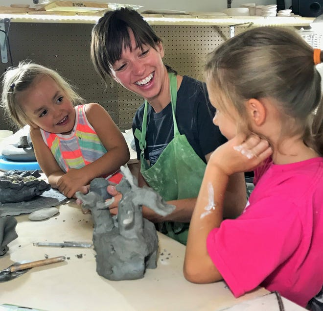 """Iowa City ceramics artist Heidi McKay Casto assists daughters Beatrice (left) and Amari with a clay sculpture in her home studio.  Balancing motherhood with a career in art is the theme for the """"Give and Take"""" exhibit Casto organized which is now on display at Public Space One.  (Photo:  Special to the Press-Citizen)"""