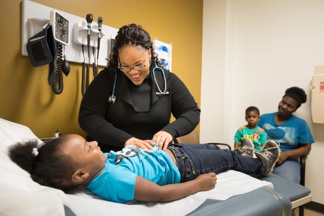 Pittman entertains Madysen Palmer, 5, while checking her breathing.