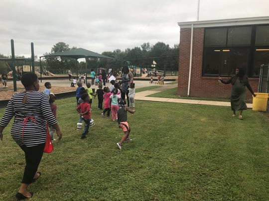 A class at Washington Douglass Head Start heads to the playground for recess while coordinator Tiffany Woods (far right) waves at them.