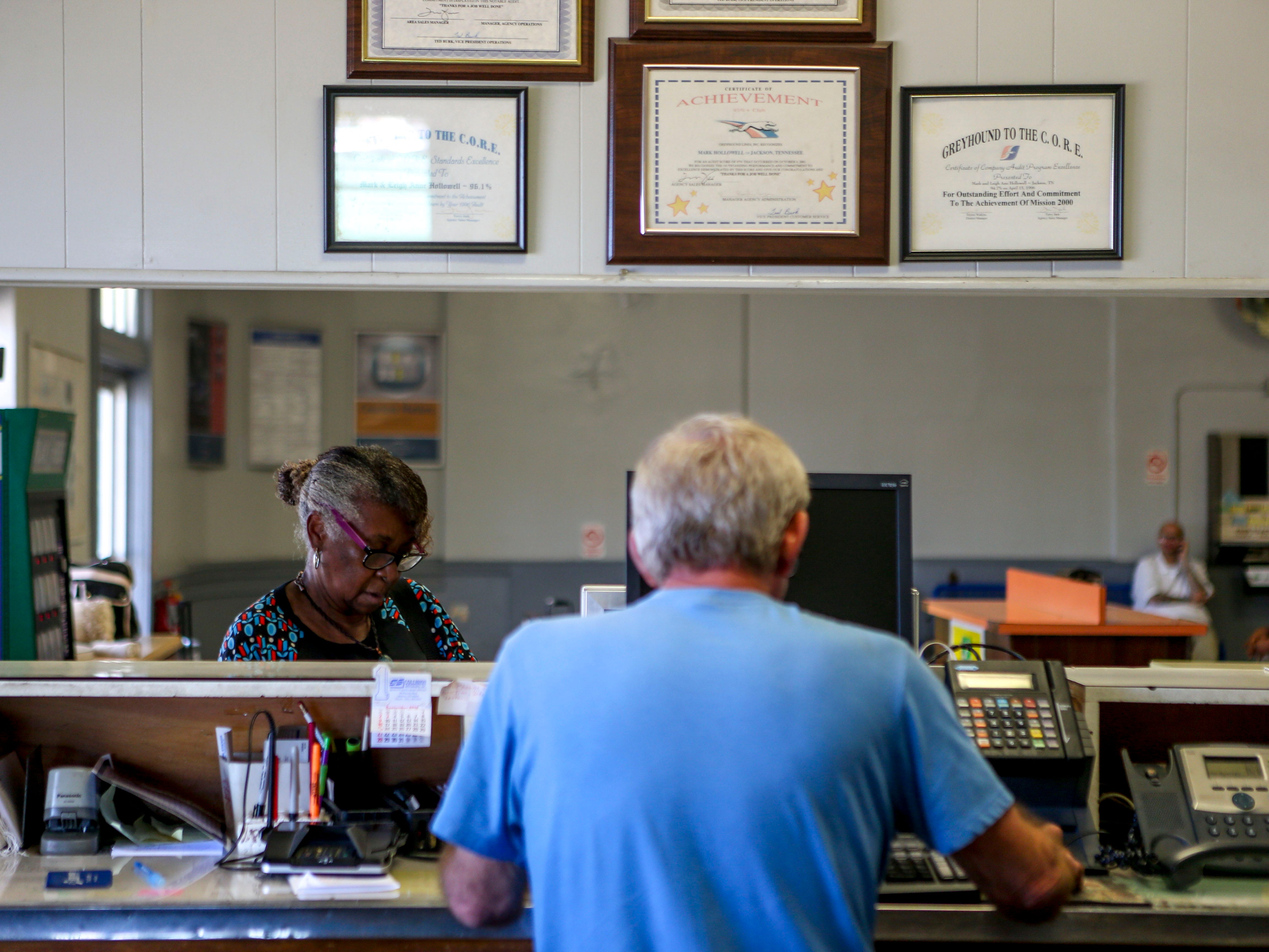 Mark Hollowell serves a customer buying a bus ticket at the Greyhound Bus Station in Jackson, Tenn., on Wednesday, Sept. 12, 2018.