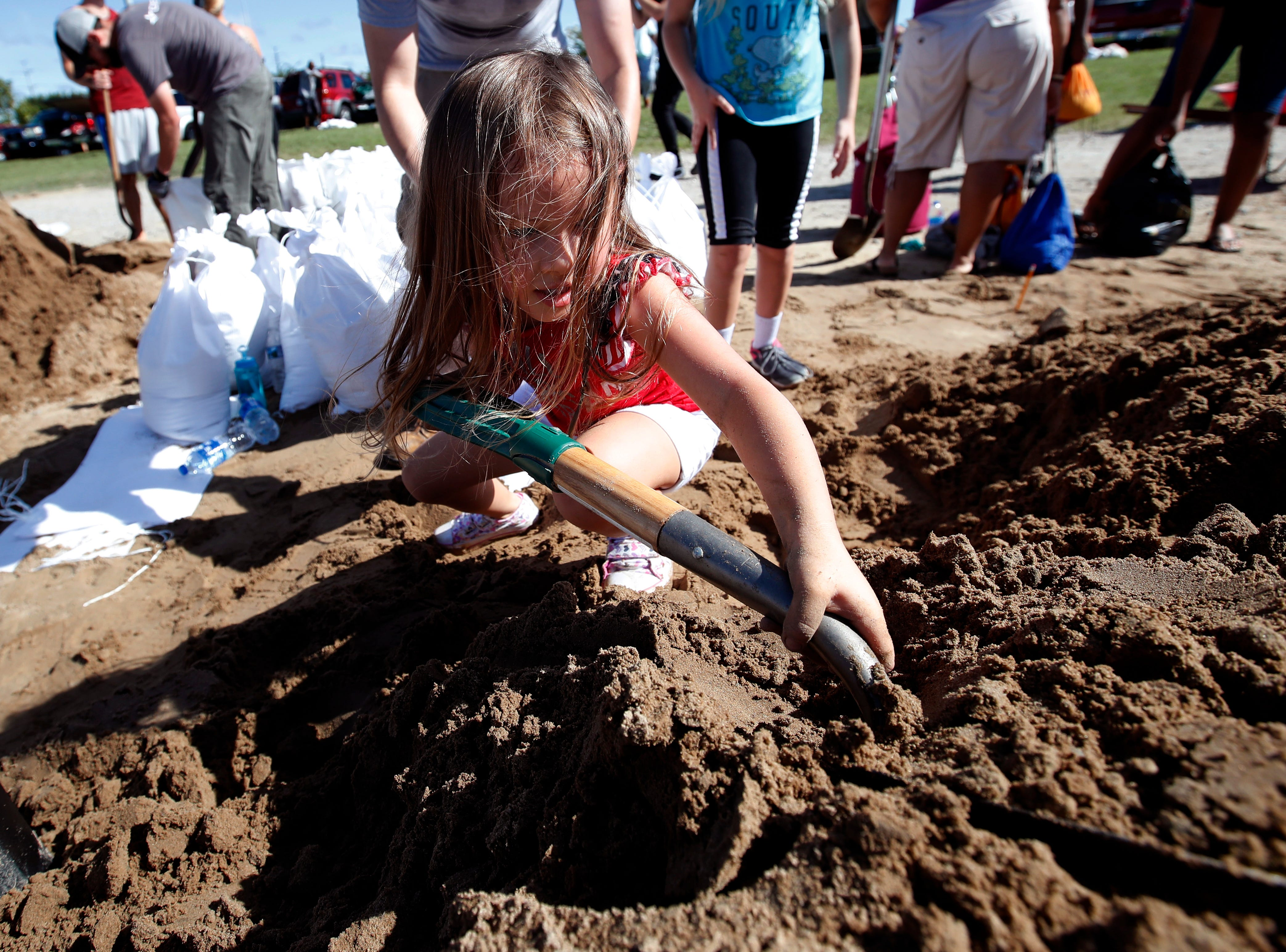 Chloe Heeden, 4, from Virginia Beach, Va., shovels sand to help her dad fill sandbags, Wednesday, Sept. 12, 2018, in Virginia Beach, Va., as Hurricane Florence moves towards the eastern shore. The National Hurricane Center's projected track had Florence hovering off the southern North Carolina coast from Thursday night until landfall Saturday morning or so, about a day later than previously expected. The track also shifted somewhat south and west, throwing Georgia into peril as Florence moves inland.