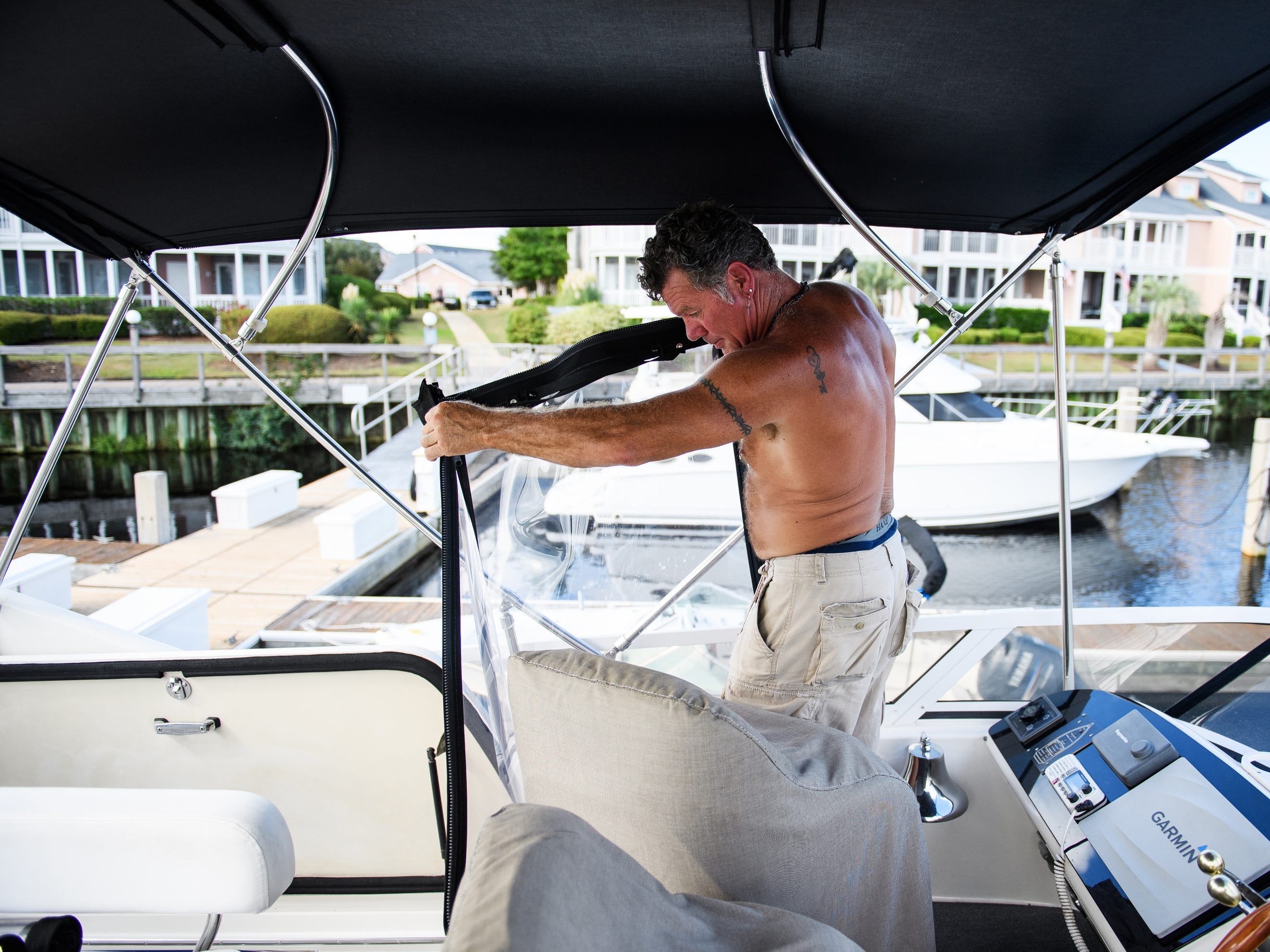 Sep 12, 2018; North Myrtle Beach, SC, USA; Masten Cloer prepares his boat for Hurricane Florence at the Lightkeepers Marina in North Myrtle Beach. Cloer, who lives in North Carolina, said he drove down to protect his new boat and will be staying on it during the hurricane.