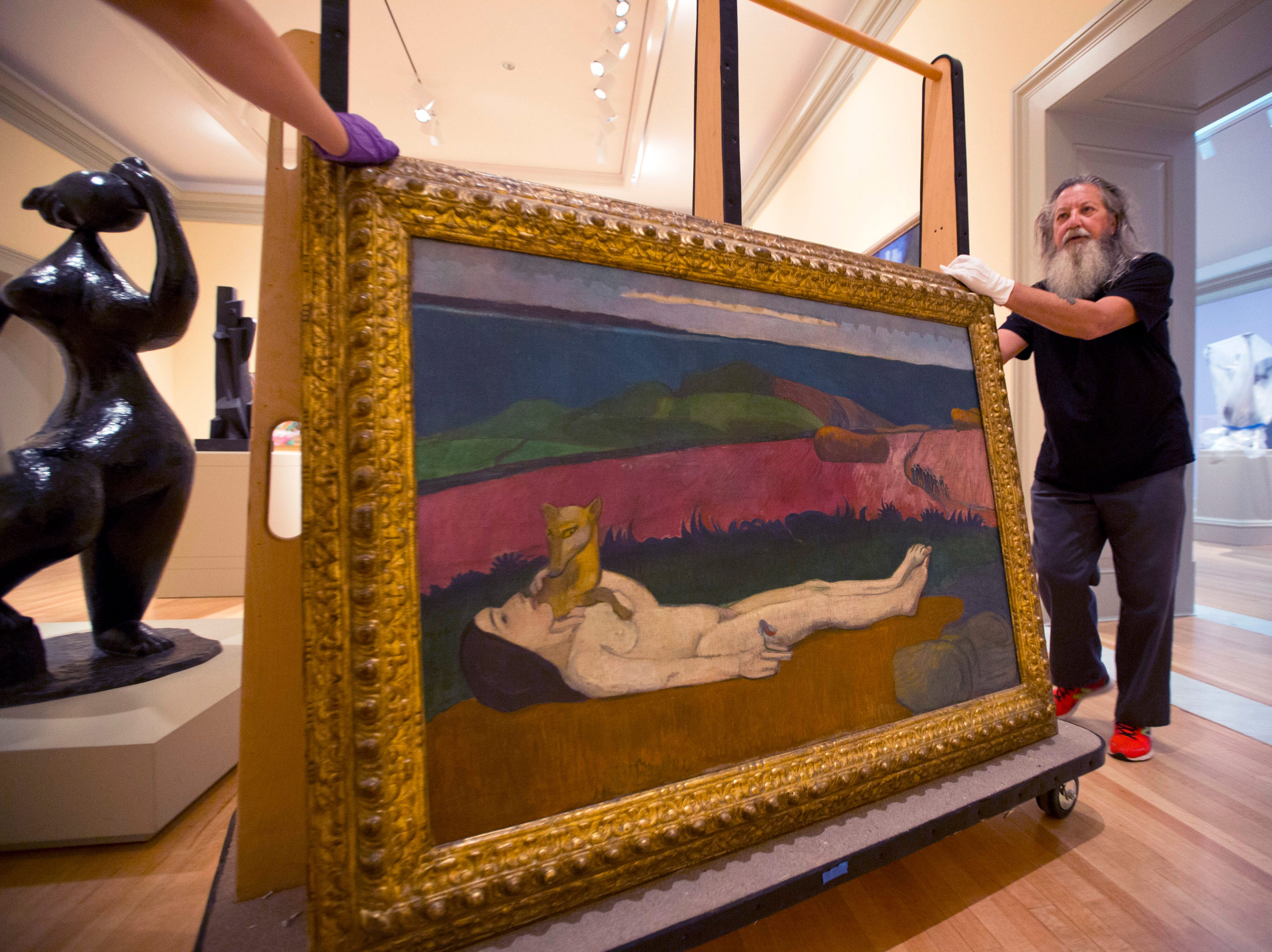 "Alisa Reynolds, left, not seen, and Richard Hovorka, right, move the painting "" The Loss of Virginity"" by Paul Gauguin at the Chrysler Museum of Art in Norfolk, Va., on Tuesday, Sept. 11, 2018. As category 4 Hurricane Florence approaches, staff members pull priceless paintings off the walls near windows and skylights on. Later on, the entrance to the museum will be sandbagged."