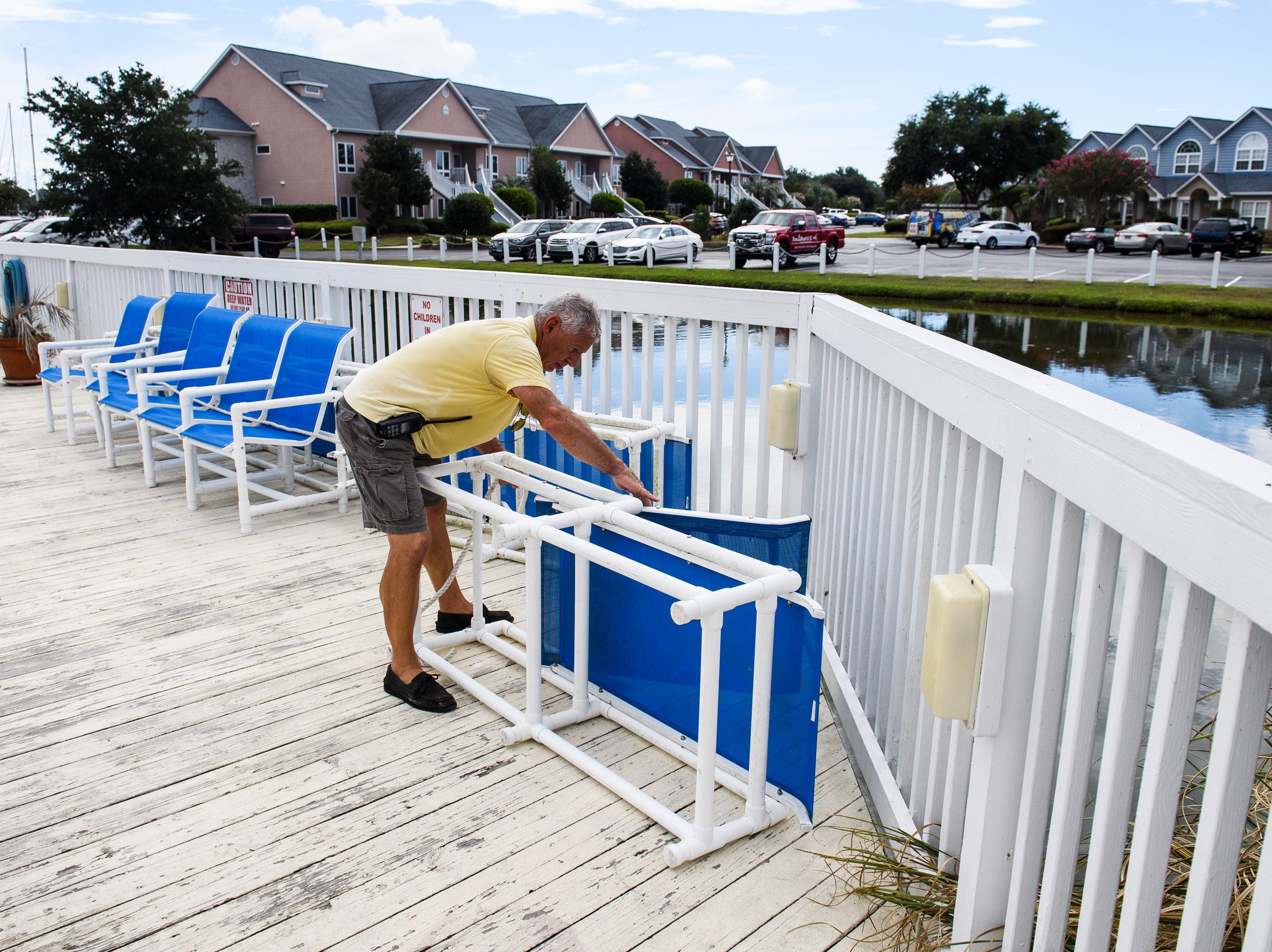 Sep 12, 2018; North Myrtle Beach, SC, USA; George Rubis, assistant dock manager at the Lightkeepers Marina, ties up sunbathing chairs at the clubhouse anticipation of Hurricane Florence.