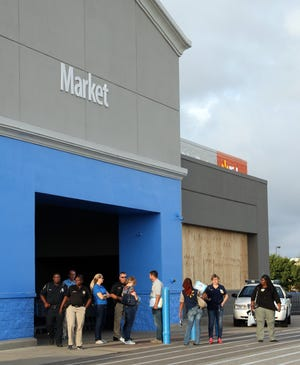 September 12, 2018; Elizabeth City, NC, USA; Walmart employees exit the store prior to it closing and boarded up in Elizabeth City, North Carolina on Wednesday.