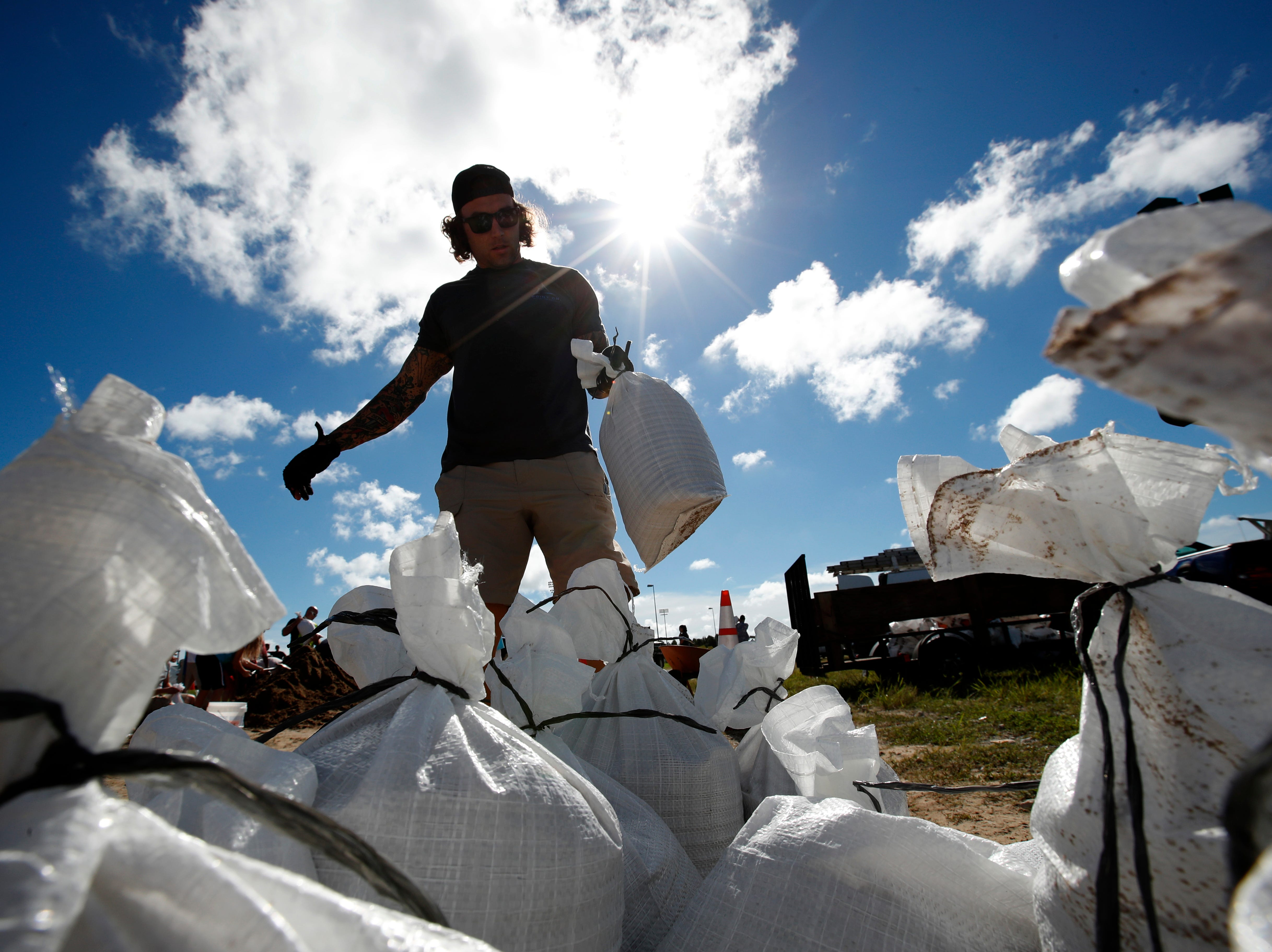 A Virginia Beach, Va., resident moves a sandbag before loading it in his truck, Wednesday, Sept. 12, 2018, in Virginia Beach, Va., as Hurricane Florence moves towards the eastern shore. The National Hurricane Center's projected track had Florence hovering off the southern North Carolina coast from Thursday night until landfall Saturday morning or so, about a day later than previously expected. The track also shifted somewhat south and west, throwing Georgia into peril as Florence moves inland.