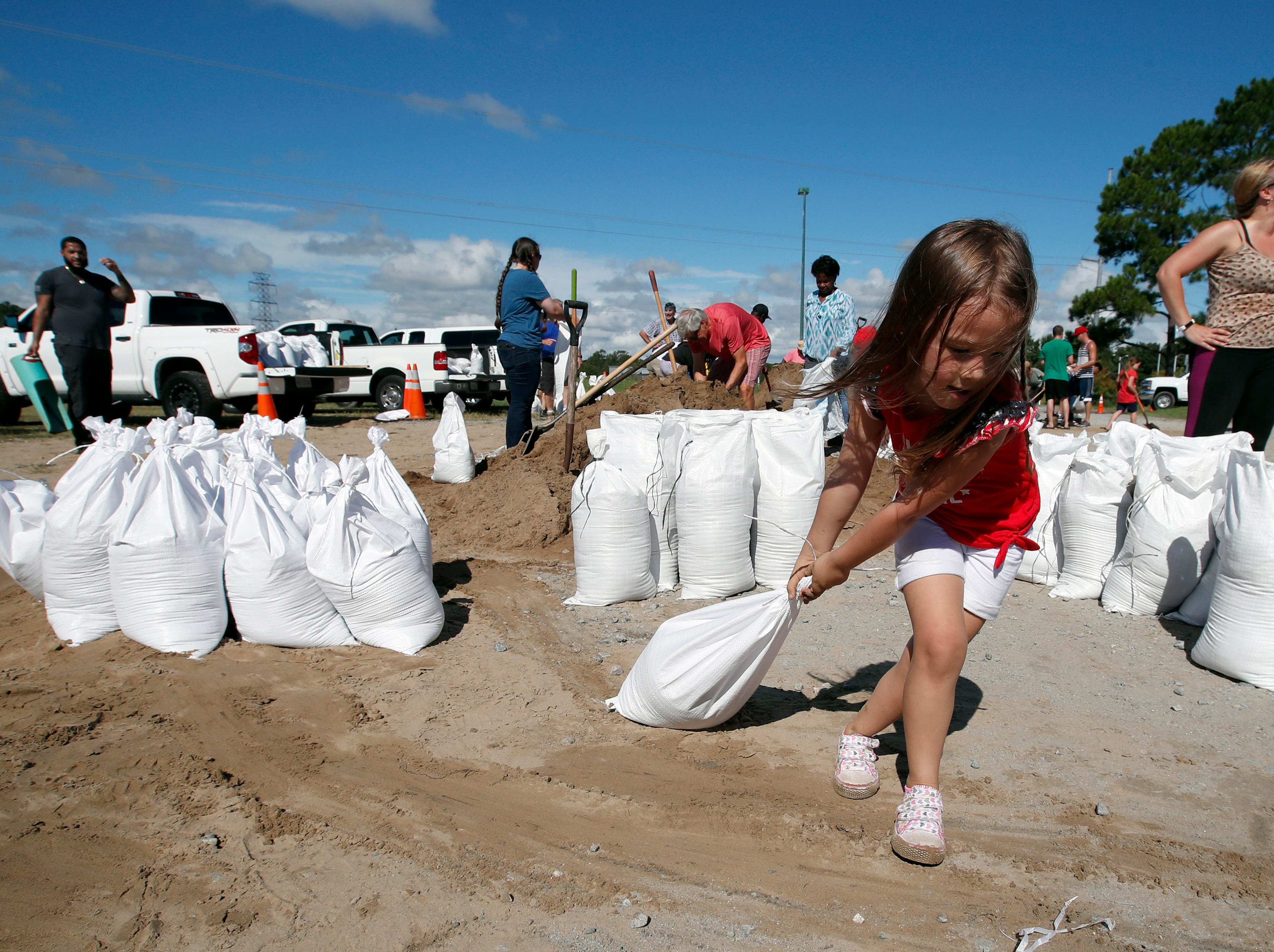 Chloe Heeden, 4, from Virginia Beach, Va., drags a sandbag to her father's car, Wednesday, Sept. 12, 2018, in Virginia Beach, Va., as Hurricane Florence moves towards the eastern shore. The National Hurricane Center's projected track had Florence hovering off the southern North Carolina coast from Thursday night until landfall Saturday morning or so, about a day later than previously expected. The track also shifted somewhat south and west, throwing Georgia into peril as Florence moves inland.