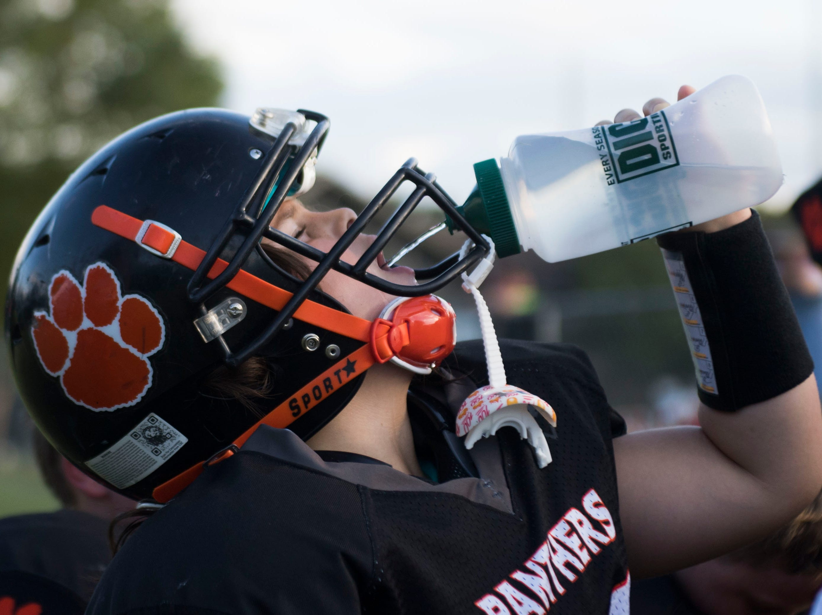 Ava Wooten, 9, of Powell, takes a drink while playing with her 9U Powell Youth football team Tuesday, Sept. 11, 2018. Ava is the only girl on her team.