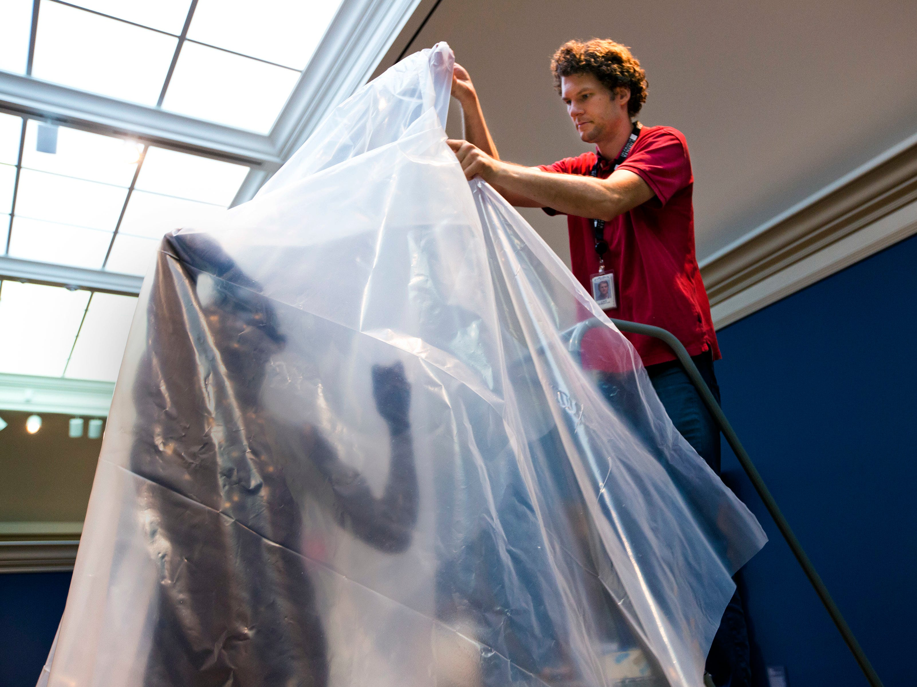 "Clark Williamson, exhibit designer, drapes the sculpture ""The Age of Bronze"" by Auguste Rodin at the Chrysler Museum of Art in Norfolk, Va., on Tuesday, Sept. 11, 2018. As category 4 Hurricane Florence approaches, staff members pull priceless paintings off the walls near windows and skylights on. Later on, the entrance to the museum will be sandbagged."