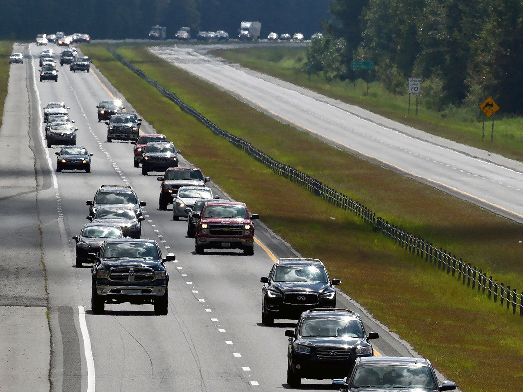 "Motorists drive down I-40 westbound as the eastbound road is empty in advance of Hurricane Florence near Suttontown, N.C. on Wednesday, Sept. 12, 2018.  North Carolina Gov. Roy Cooper is urging residents in evacuation zones to move to safety, saying the effects of Hurricane Florence are ""only hours away."""