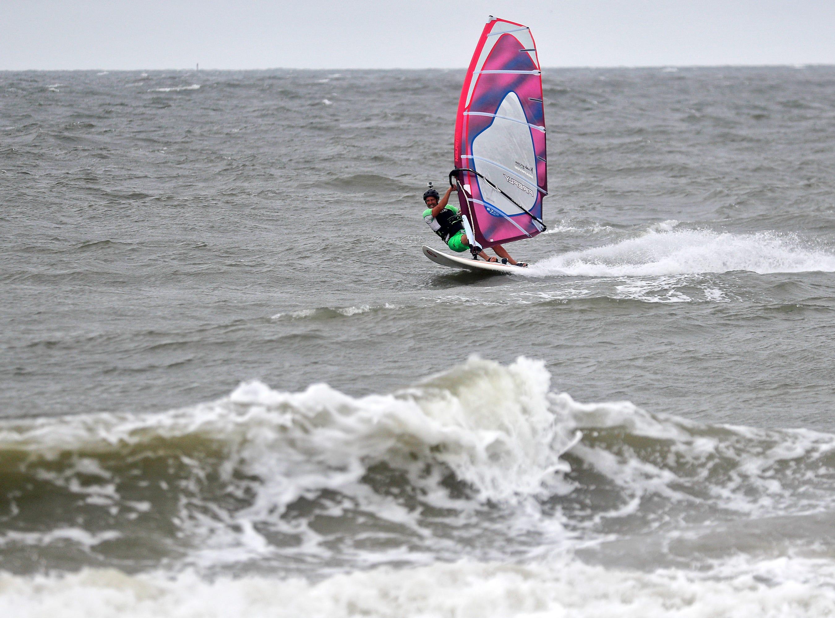 Keith Knight windsurfs through the waves at Buckroe Beach in Hampton, Va., Thursday, Sept. 13, 2018 as Hurricane Florence approaches the coast.
