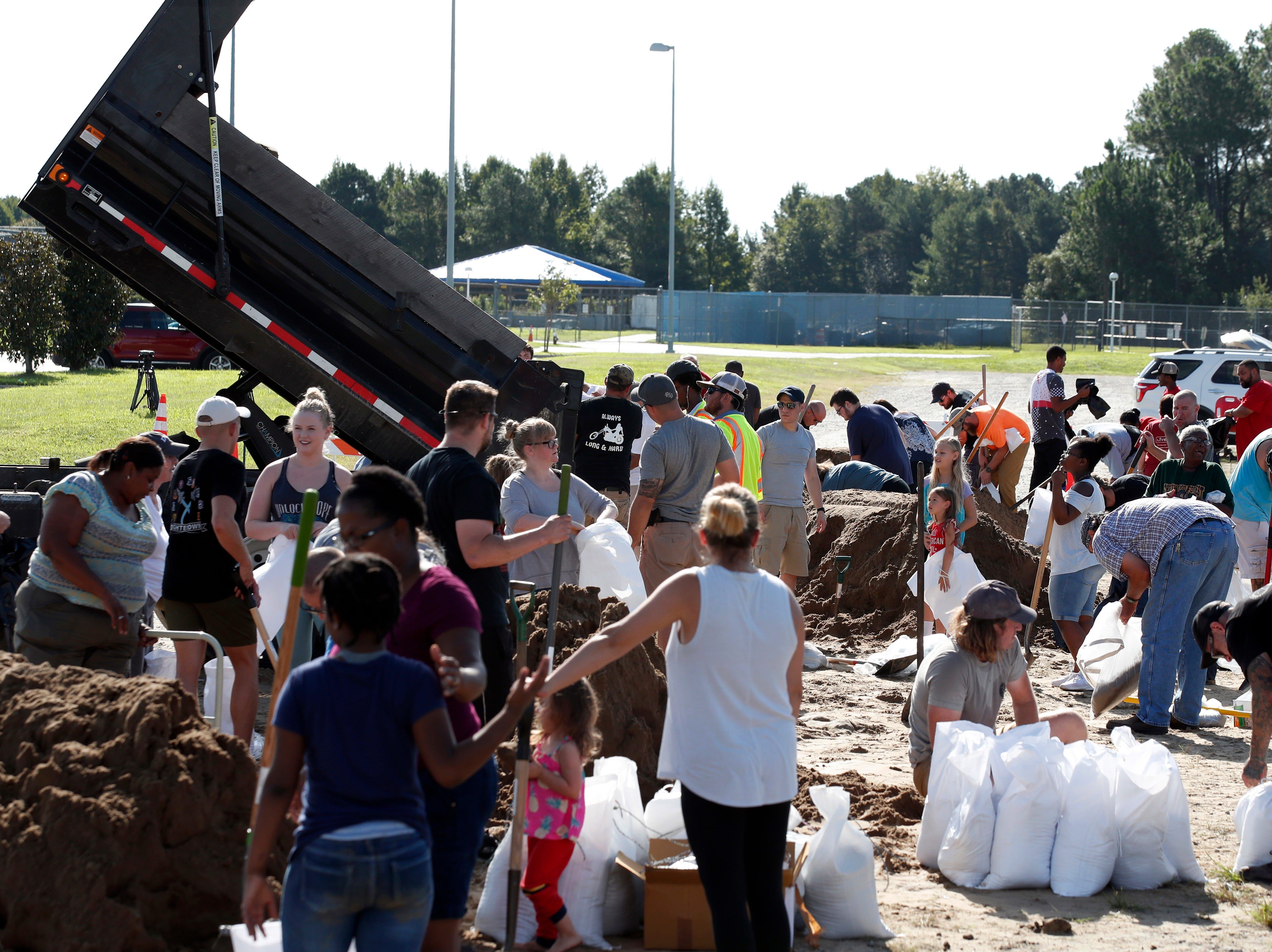 As a truck dumps more sand, residents fill sandbags, Wednesday, Sept. 12, 2018, in Virginia Beach, Va., as Hurricane Florence moves towards the eastern shore. The National Hurricane Center's projected track had Florence hovering off the southern North Carolina coast from Thursday night until landfall Saturday morning or so, about a day later than previously expected. The track also shifted somewhat south and west, throwing Georgia into peril as Florence moves inland.