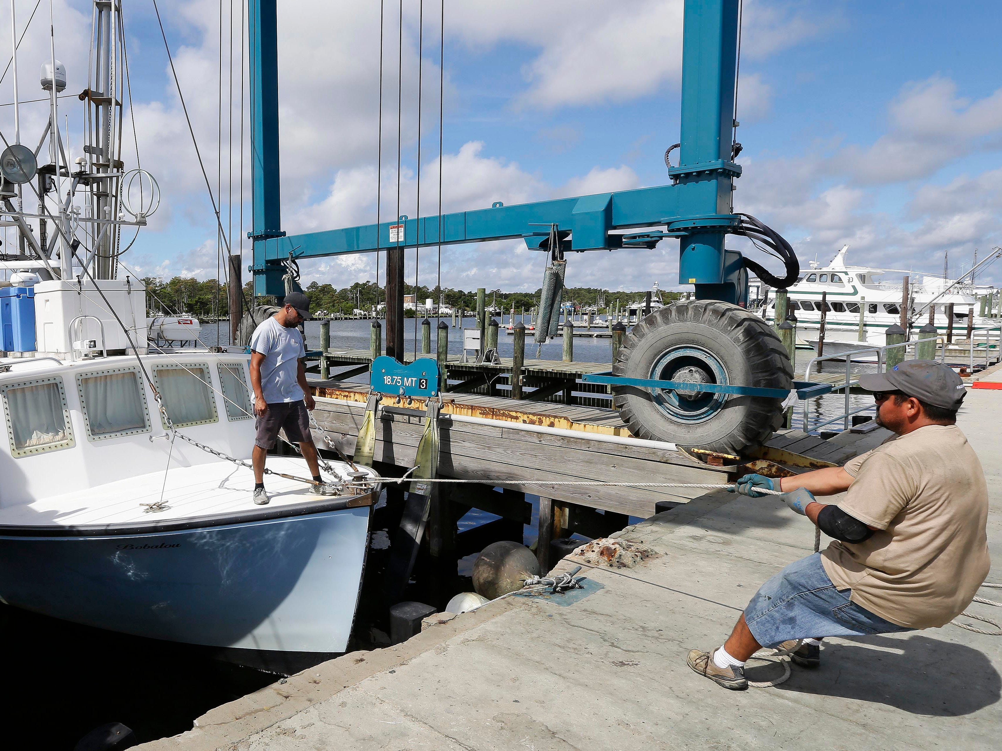 "Workers remove boats from the water in Wanchese Harbor as Hurricane Florence approaches the coast of the Carolinas in Wanchese, N.C., Wednesday, Sept. 12, 2018. The National Weather Service says Hurricane Florence ""will likely be the storm of a lifetime for portions of the Carolina coast."""