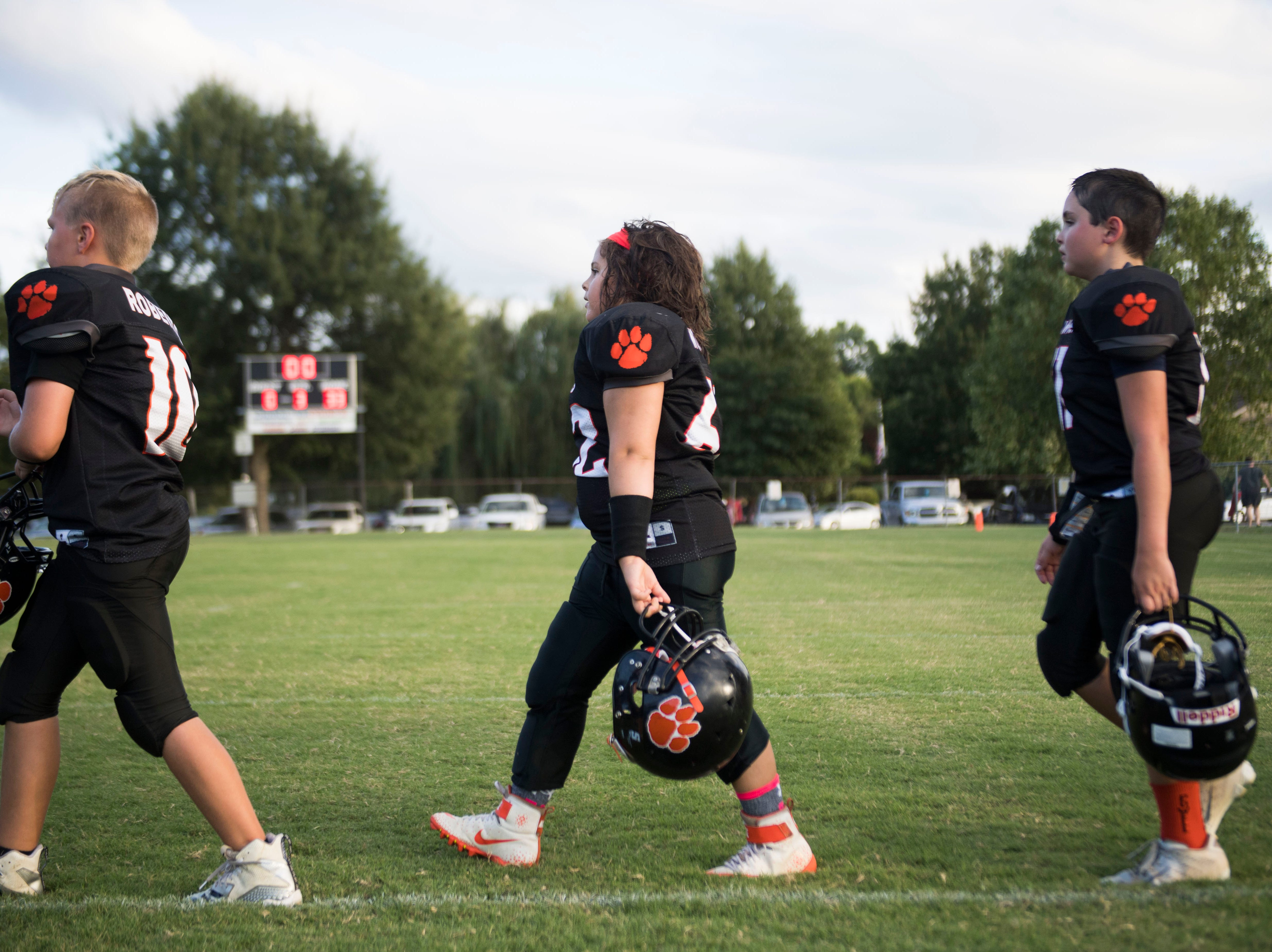 Ava Wooten, 9, of Powell, walks on the field with her 9U Powell Youth football team Tuesday, Sept. 11, 2018. Wooten is the only girl on her team.