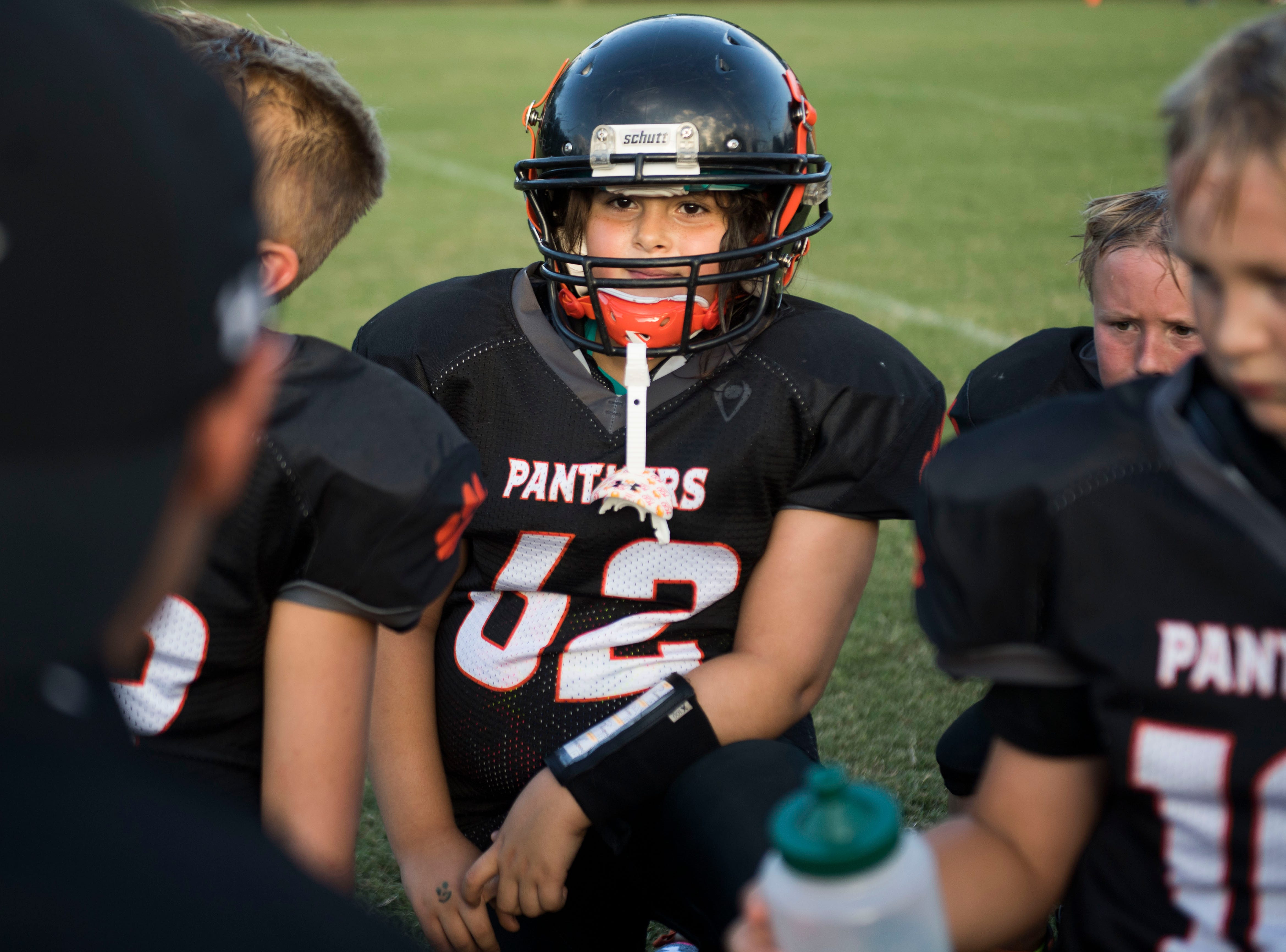 Ava Wooten, 9, of Powell, listens to her 9U Powell Youth football coach during a game Tuesday, Sept. 11, 2018. Ava is the only girl on her team.