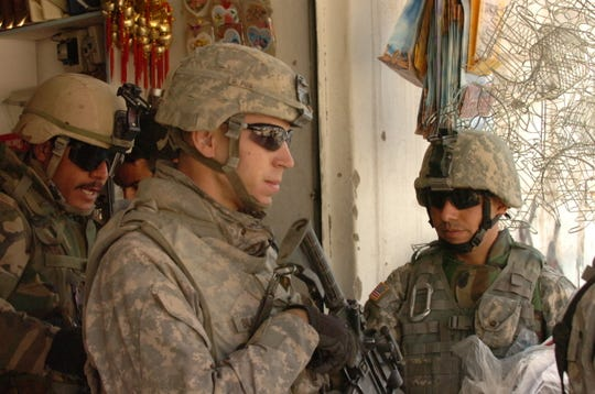 Lt. Tommy Blackburn, center, and interpreter Ahmed Mardinly, stop to talk with shop owners in Mosul, Iraq, during a patrol mission in 2008. Both saved the other's life and are now as close as brothers. Mardinly becomes a U.S. citizen on Friday. And yes, Blackburn, a Purdue ROTC grad, will be there for the ceremony.
