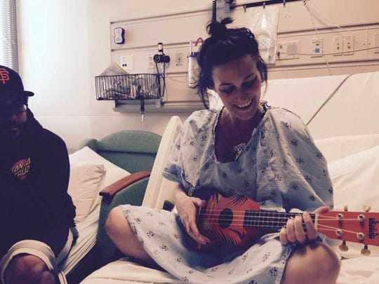 Elizabeth plays the guitar while in her hospital bed.