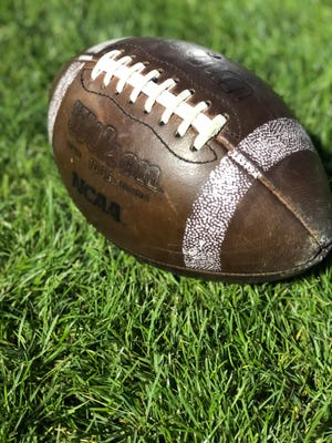 A football sits on the grass at East Lansing High School.
