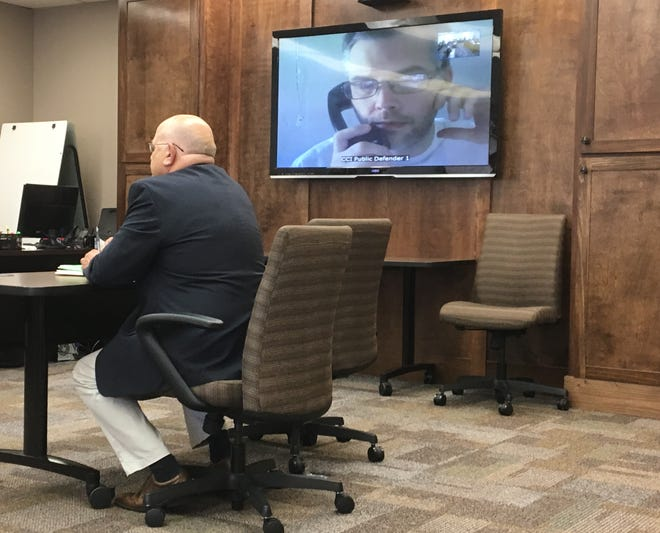 Shawn Grate appears at an arraignment via video conference Thursday, Sept. 13, 2018. Richland County Prosecutor Gary Bishop sits in the foreground.