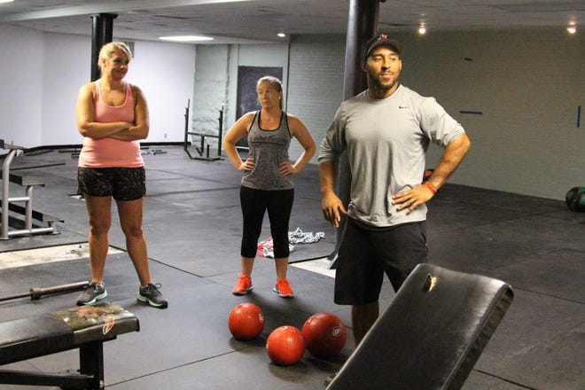 Bryceson Lawrence stands with a group of clients at his new gym Phase 6 Strength and Performance,  162 W. Center St., on Wednesday.
