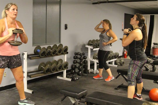 Angie Kloha, Mikki Paxton and Ann Marie Urso sweat during a Wednesday afternoon workout at Phase 6 Strength and Performance. The business officially opened on Monday.