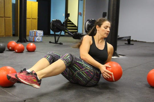 Ann Marie Urso picks up a weighted ball during her Wednesday afternoon workout. She has been training with  Bryceson Lawrence for almost a year and followed him to his new location on West Center Street.