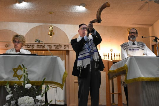Max Stein blows the shofar, or ram's horn, flanked by cantorial soloist Hari Jacobsen and Rabbi Mark Gross.