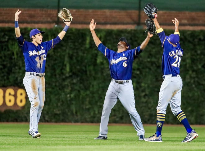 Outfielders Christian Yelich (from left) Lorenzo Cain and Curtis Granderson  celebrate after the Brewers beat the Cubs, 5-1, to close within one game of Chicago for the NL Central lead on Wednesday night.