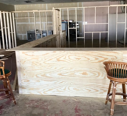 Work to turn two storefronts into one restaurant for the new site of BigCountry's Barbecue includes construction of a bar.