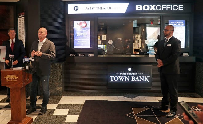 Gary Witt, CEO of The Pabst Theater Group, announces a new branding agreement with Town Bank. At left, Jay Mack, president and CEO of Town Bank, and at right, Joaquin Altoro, vice president of commercial banking at Town Bank, listen as The Pabst Theater Group unveils a newly redesigned box office for the Pabst Theater.