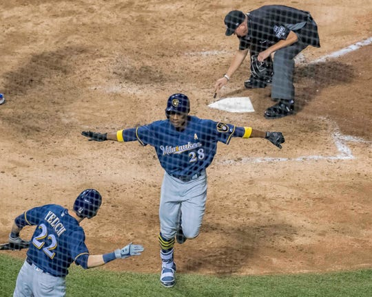 Curtis Granderson gets ready to smack hands with Christian Yelich on his way back the Brewers dugout after he hit a solo homer in the ninth inning against the Cubs on Wednesday night.