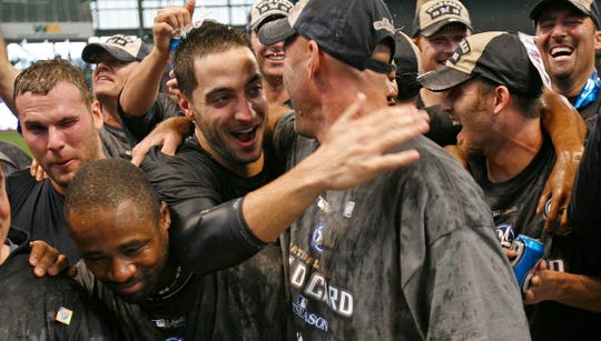 Ryan Braun, center, gives manager Dale Sveum a hug among champagne soaked players during celebration after their win Sunday at Miller Park over the Chicago Cubs.