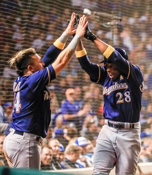 Brewers shortstop Hernan Perez greets Curtis Granderson after Granderson's home run in the ninth inning Wednesday night at Wrigley Field.