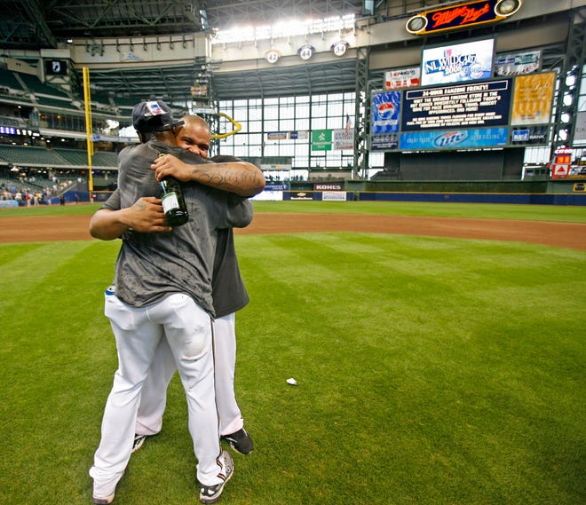 """Prince Fielder sports a """"blessed"""" tattoo on his arm holding champagne and getting a hug from Mike Cameraon on the field after their victory over the Cubs to win the Wild card at Miller Park."""
