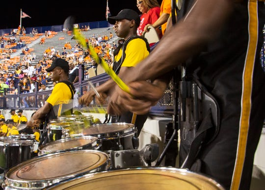 A member of the Mighty Marching Hornet's tenor line taps on each drum head during the fourth quarter.