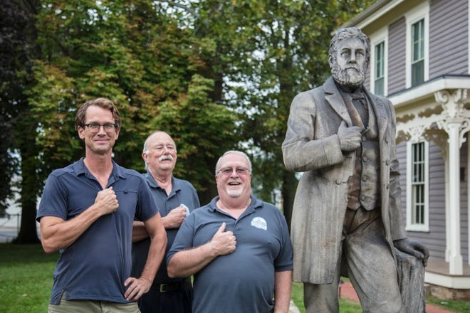 Members of the Delaware County Historical Society pose beside the Charles Willard statue in Muncie.