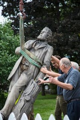 Members of the Delaware County Historical Society help lower the Charles Willard statue to the ground in Muncie.
