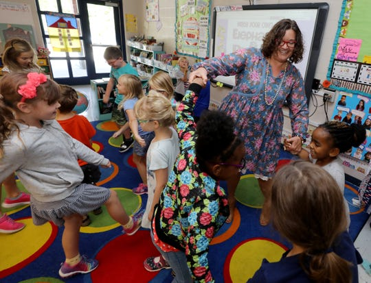 Teacher Melissa Miller dances with her students after completing a lesson on Sept. 12.