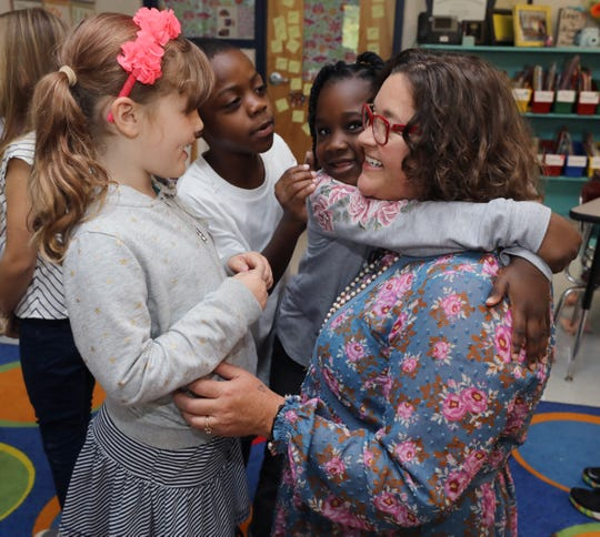 Melissa Miller, right, with students Vera McIntosh, left, Kevon Leach, middle, and Za'Niyah Brown, center right, in their first-grade classroom at Franklin Elementary School.