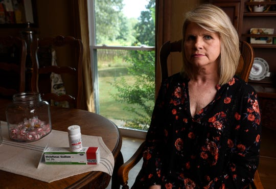 Gina Brown, 54, sits in her family's fifth-generation farm in rural Tennessee. On the table is the medicine she is prescribed for lingering pains from a crushed pelvis she suffered years ago.