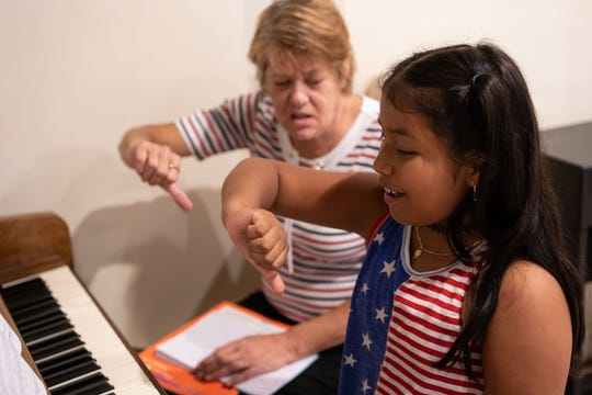 The third piano lesson for nine-year-old Naomi Hernandez of Bonita Springs was to learn how to get to a higher pitch without cracking and being breathless. Using a hand-motion technique, Judy Murphy helps Hernandez to be in tune while at a higher pitch.