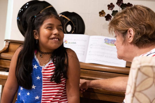 """Is it..."" the nine-year-old Naomi Hernandez pauses to listen carefully at the note her teacher, Judy Murphy plays on the piano to test Hernandez's progress. Completion a lesson successfully is rewarded by a sticker for their piano book."
