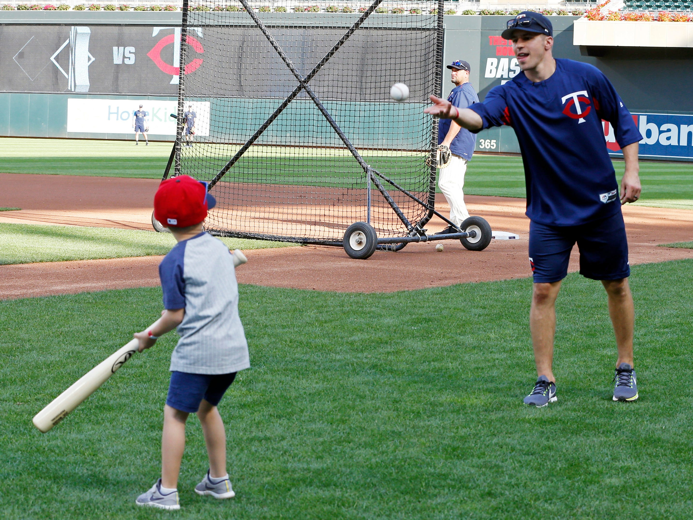 Minnesota Wild's Zach Parise, a former captain with the New Jersey Devils, throws to his son Jackson before the Minnesota Twins batting practice and a baseball game against the New York Yankees as several players of the NHL hockey team visited Target Field Wednesday, Sept. 12, 2018, in Minneapolis. The Wild open training camp Thursday in St Paul, Minn.