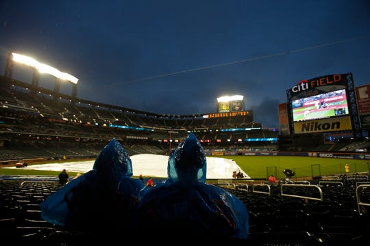 Fans wait out a rain delay prior to the first game of a scheduled doubleheader between the Miami Marlins and the New York Mets at Citi Field on Wednesday, Sept. 12, 2018.