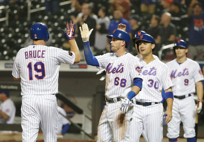 New York Mets' Jay Bruce (19) celebrates with teammates Jeff McNeil (68) and Michael Conforto (30) after hitting a grand slam home run during the sixth inning of a baseball game against the Miami Marlins Wednesday, Sept. 12, 2018, in New York.