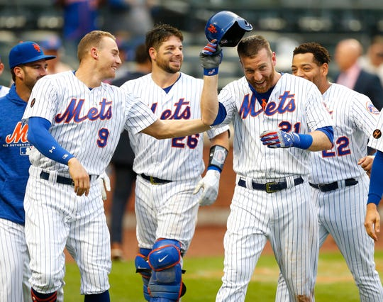 Sep 13, 2018; New York City, NY, USA; New York Mets third baseman Todd Frazier (21) celebrates with teammates after hitting a walk off home run in the ninth inning to defeat the Miami Marlins 4-3  at Citi Field. Mandatory Credit: Noah K. Murray-USA TODAY Sports
